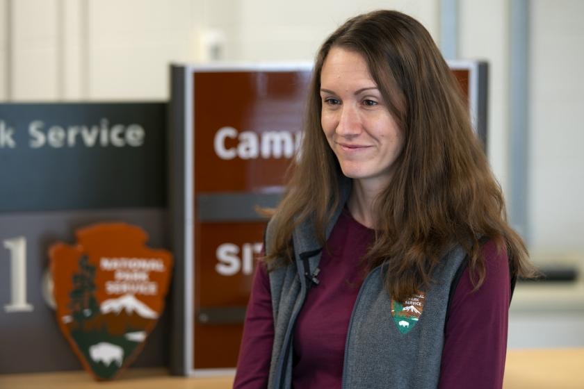 La especialista en información visual Laura Thomas posa para una foto frente a los letreros de NPS