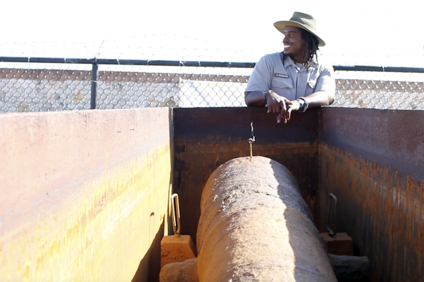 Maintenance Worker Norman Rutherford smiles next to a historic cannon at San Juan National Historic Site